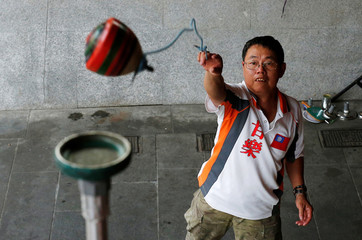 Sanxia Pinpoint Spinning Top Team captain Tseng Kuo-Hua throws a spinning top onto a 2.8 meters high platform at Sanxia old street in New Taipei City, Taiwan