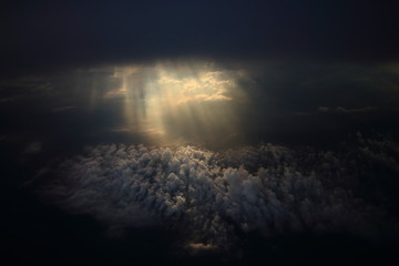 Rays of light shining through dark clouds on another cloud layer for background