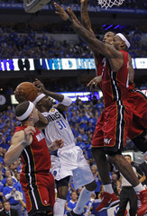 Miami Heat's LeBron James (R) and Udonis Haslem (2nd-R) put up a wall against Dallas Mavericks' Jason Terry (31) as the Heat's Mike Bibby (L) looks on during Game 3 of the NBA Finals basketball series in Dallas