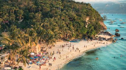 Beautiful Diniwid Beach full of people on Boracay, Philippines, during sunset