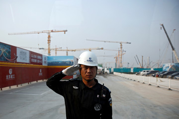 A security officer salutes at the entrance to the construction site of the terminal for the Beijing New Airport in Beijing