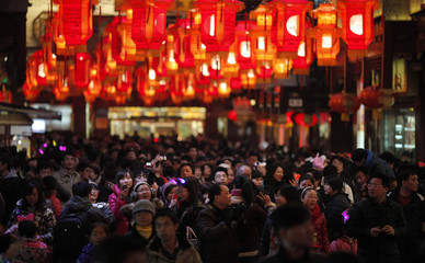 People walk in an area decorated with lanterns ahead of the Lantern Festival at Yu Yuan Garden in downtown Shanghai