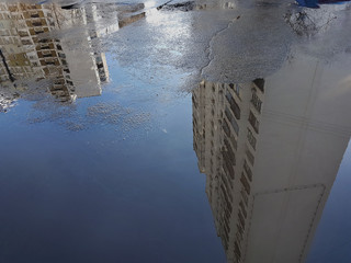 Puddle: on the surface of the blue water are reflected white many storey buildings, on the left bottom there is an empty space for the text.