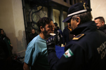 Demonstrator uses his mouth to hand over his identity card to a local police officer during a protest in Malaga