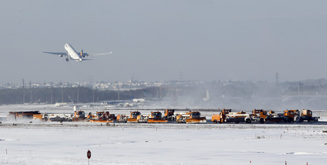 Snowploughs clear runways as a Lufthansa airplane takes off after snowfall at Frankfurt's airport