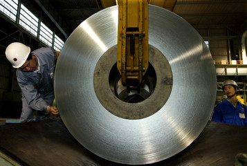 Chinese workers unload a roll of tin plate at Baosteel plant on the outskirts of Shanghai November 2..