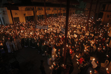 Catholics hold candles and posters with the image of lawyer Le Quoc Quan during a mass prayer for Quan at Thai Ha church in Hanoi