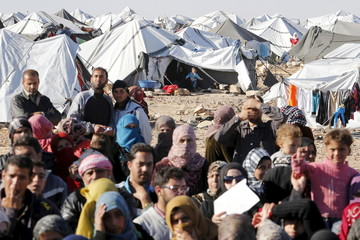 Syrian refugees stuck between the Jordanian and Syrian borders, wait to cross into Jordan after a group of them crossed into Jordanian territory, near the town of Ruwaished, at the Hadalat area, east of the capital Amman