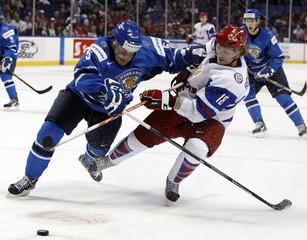 Finland's Nico Manelius checks Russia's Stanislav Bocharov in Buffalo, New York