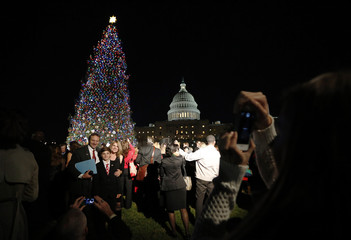 A family have their picture taken during the official lighting ceremony of the U.S. Capitol Christmas Tree in Washington