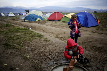 Migrant child washes his shoes at a makeshift camp on the Greek-Macedonian border, near the village of Idomeni