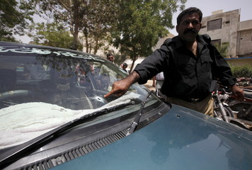 Policeman points for the media at a bullet hole on a car belonged to Syed Waheed ur Rehman, an assistant professor at the Mass Communication Department of University of Karachi who was shot dead by gunmen, in Karachi