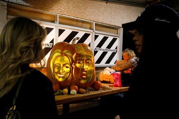 People take a look at a giant pumpkin with the faces of 2016 Democratic nominee Clinton and Republican presidential nominee Trump in New York