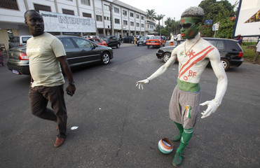 A man looks at a fan of the Ivory Coast national soccer team, with his body painted in the team's colours, on a street in Abidjan