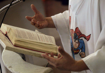 Catholic priest Alvarez officiates mass while wearing a robe with an image of cartoon character Superman at the Ojo de Agua church in Saltillo
