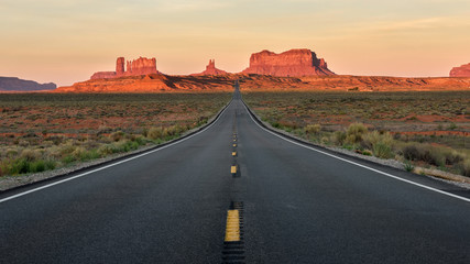 Fotobehang Lichtroze Straight Road vanishing into Monument Valley