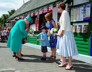 Britain's Queen Elizabeth is presented with a posy of flowers by Daniel Dixon as she arrives at Bowness-on-Windermere Pier, in Cumbria, northern England