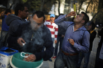 A man smokes a joint as another uses a water bottle bong during a rally for marijuana legalization in Mexico City