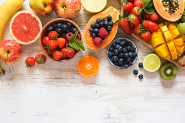 Wall Mural - Variety of fruits, strawberries, blueberries, mango, orange, grapefruit, banana, apple, grapes, kiwis on the white background, copy space for text, selective focus