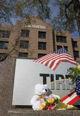 A tribute of flags, flowers and a teddy bear adorns the sign outside the rehabilitation center where U.S. Representative Giffords is to receive treatment in Houston