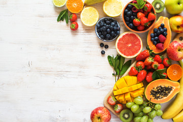 Wall Mural - Above view of colorful fruits, strawberries, blueberries, mango, orange, grapefruit, banana, apple, grapes, kiwis on the white background, copy space for text, selective focus
