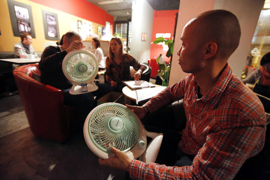 People unwrap plastic fans during a workshop organized by Smart Air Filters at a local coffee shop in Shanghai