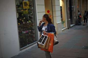 A woman looks at the showcase of a shoe store as she holds shopping bags during the Black Friday sales in downtown Malaga
