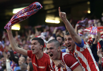 Atletico Madrid supporters celebrate their first goal during their Champions League final soccer match against Real Madrid at a fan zone at Vicente Calderon stadium in Madrid