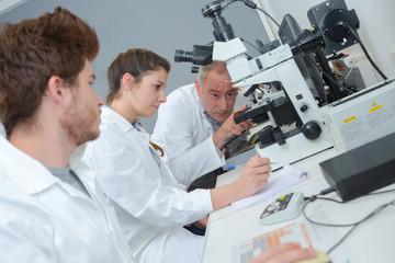 Teacher instructing students on use of microscope