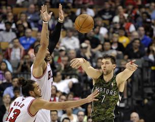 Raptors forward Bargnani passes the ball past Bulls defenders Boozer and Noah during their NBA game in Toronto