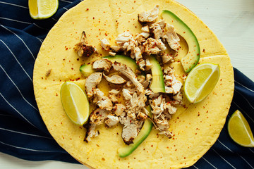 Tortilla with chicken, avocado and lime top view