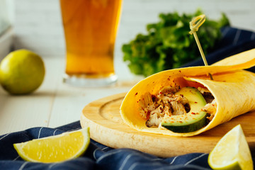 Wrap with chicken and avocado on wooden plate