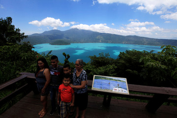 A family pose for a picture with the Coatepeque Lake as background in the town of El Congo