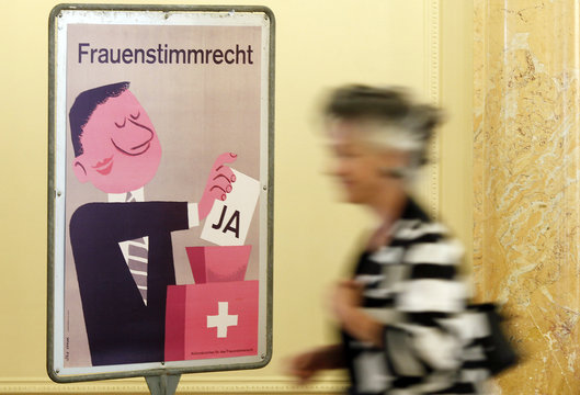 A woman passes a vintage poster before an event to celebrate 40 years of Swiss women's suffrage in Bern
