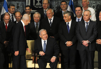 Israel's Prime Minister Netanyahu and President Peres talk to ministers after posing for a group photo in Jerusalem