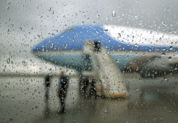 Air Force One is pictured through a window in the rain as Obama arrives in Brussels for the G7