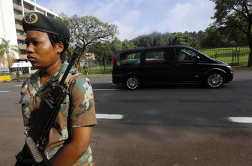 Soldier stands guard as the funeral cortege carrying the coffin of former South African President Nelson Mandela passes by close to the Union Buildings in Pretoria