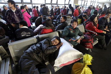 A passenger sleeps in the crowded waiting room at West Railway Station in Beijing