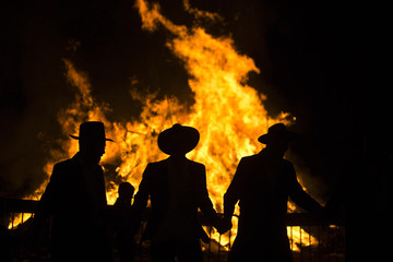 Ultra Orthodox Jews are silhouetted against a bonfire during celebrations for the Jewish holiday of Lag Ba'Omer in Kfar Chabad, near Lod