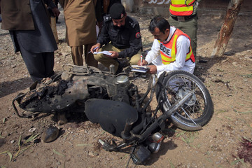 Police and rescue worker inspect a damaged motorbike at the site of suspected suicide bomb attack in the outskirts of Peshawar