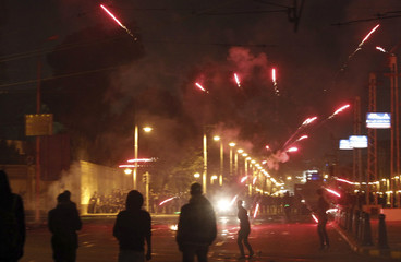 Protesters, who oppose Egyptian President Mohamed Mursi, throw fireworks and flee from teargas released by riot police during clashes in front of the presidential palace in Cairo