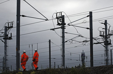 Network Rail workers walk along a railway track in London