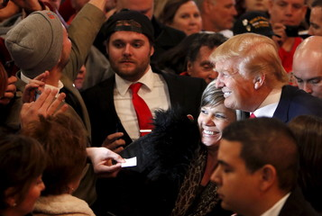 Republican U.S. presidential candidate Donald Trump takes photos with supporters after a campaign event at the Surf Ballroom in Clear Lake, Iowa