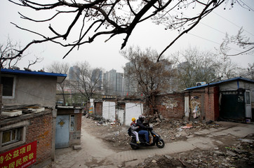 A man rides an electric bike, carrying his son home in an old residential area in central Beijing
