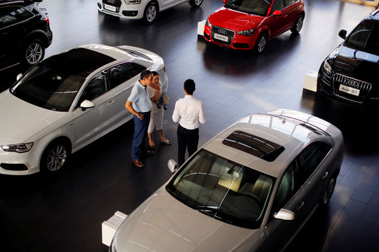 Customers look at cars at an Audi dealership from the Baoxin Auto Group in Shanghai