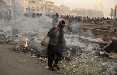 A boy walks past a garbage dump in Kabul