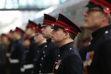 Members of military personnel wear poppies in their caps as they line the platform after a train with commemorative wrap for the fallen of World War I pulled into the station at King's Cross in London