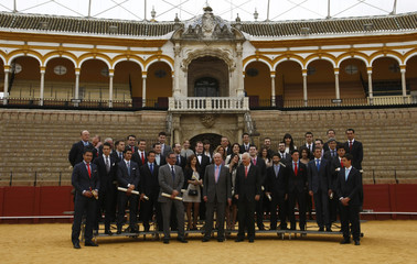 Spain's King Juan Carlos poses for a group photo with members of differents Spanish governments and prizewinning bullfight trophies and university students in Seville