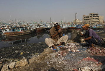 A man pauses to smoke a cigarette while cleaning fish at Karachi's Fish Harbour