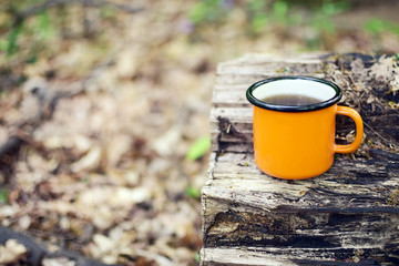 Enamel cup of coffee stands on a log